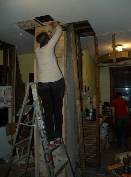 a new wall, of 2x4s and plywood, is being put in in front of the chimney