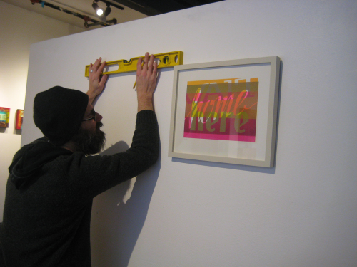 Neal uses a level to hang a framed print on the gallery wall