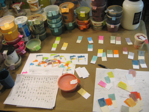 table with strips of paper, ink containers, and diagrams on it