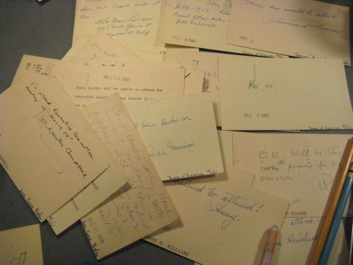 a pile of postcards on manila paper with various handwriting on them