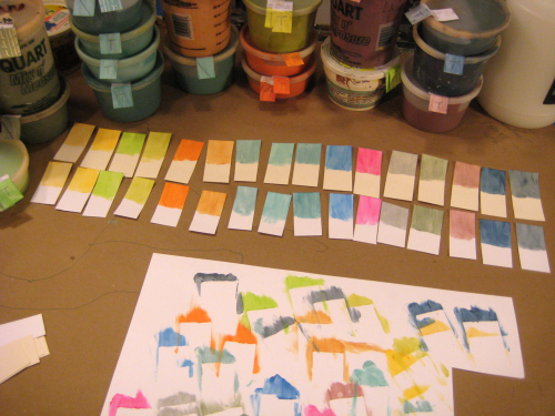 jars of ink and test color strips, laid out on a desk