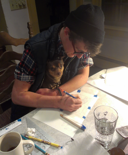 a person seated at a table trying to draw with a small dog on their lap