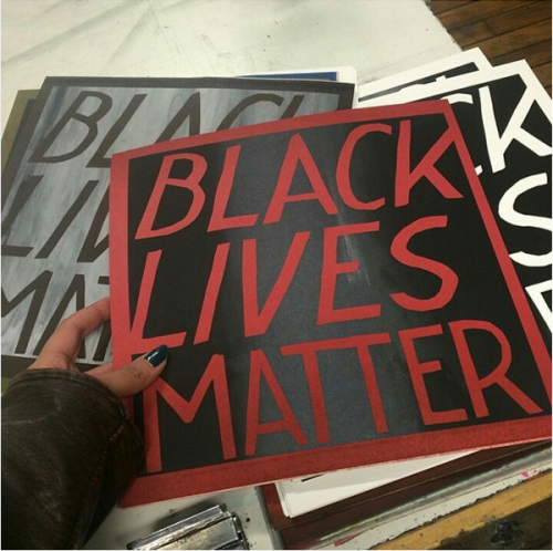 a hand with black nail polish pointing to a pile of screenprinted signs that say: Black Lives Matter